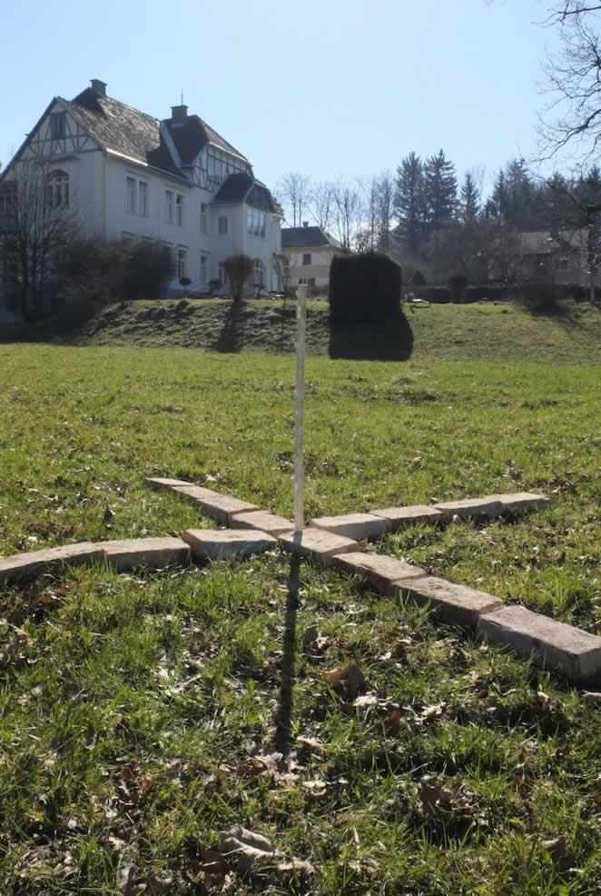 Ein Kreuz aus Ziegelsteinen liegt in einer Wiese, im Hintergrund eine Villa, im Vordergrund ein Messstab.