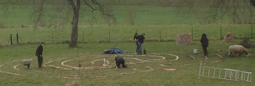 Frauen legen ein Labyrinth aus Ziegelsteinen in die Wiese.
